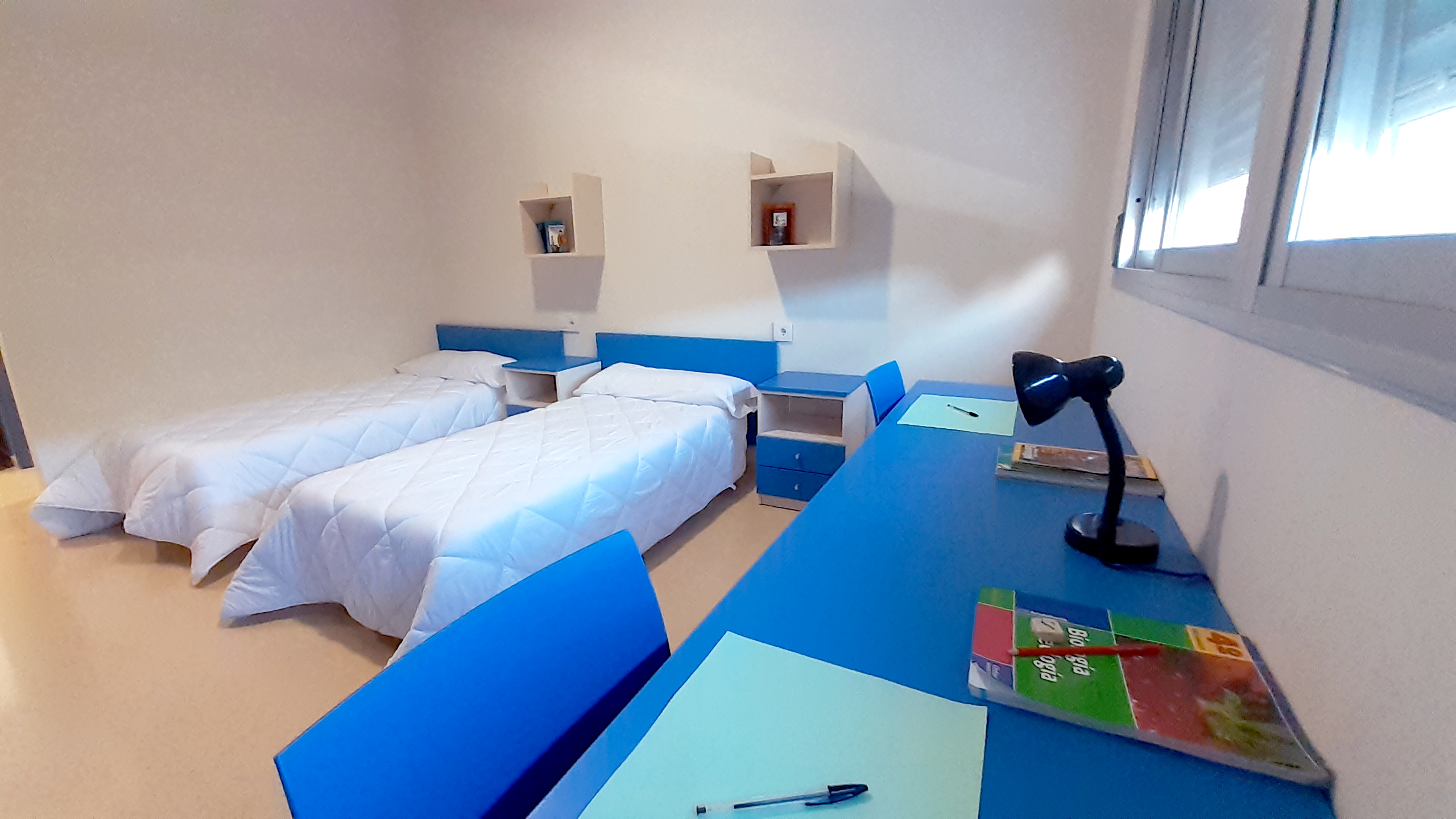 Escritorio y camas con tonos azules en una de las habitaciones del colegio residencial