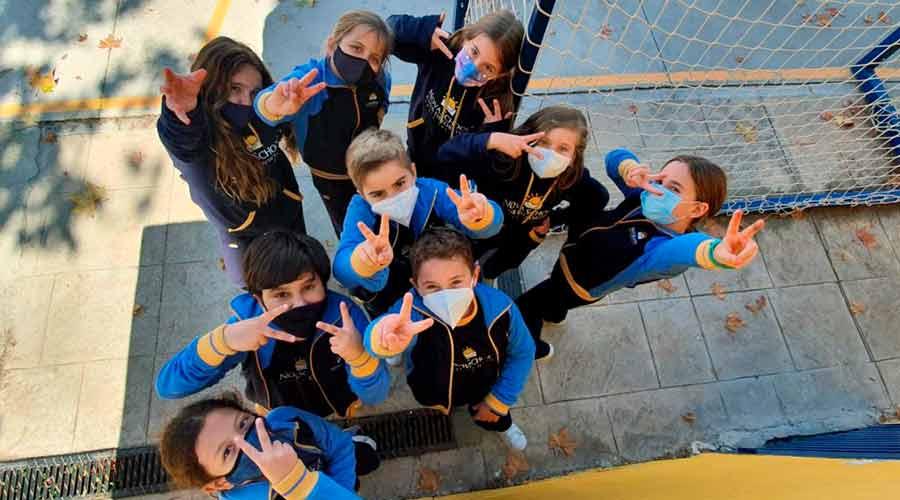 Grupo de alumnos de primaria haciendo el signo de la victoria con sus manos