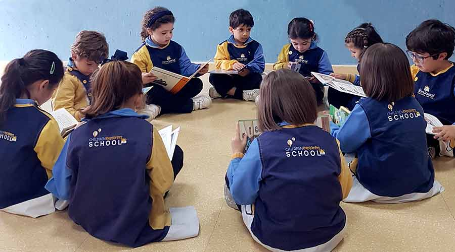 Alumnos y alumnas de segundo ciclo de infantil leyendo en círculo