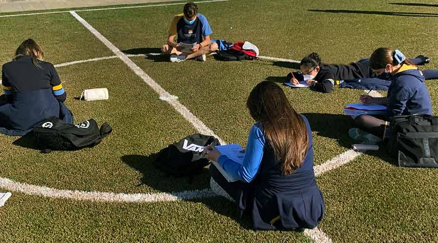 Estudiantes de Secundaria sentados en círculo en el centro del campo de fútbol con césped artificial